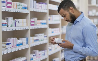 Man reading label of medicine bottle - stock photo