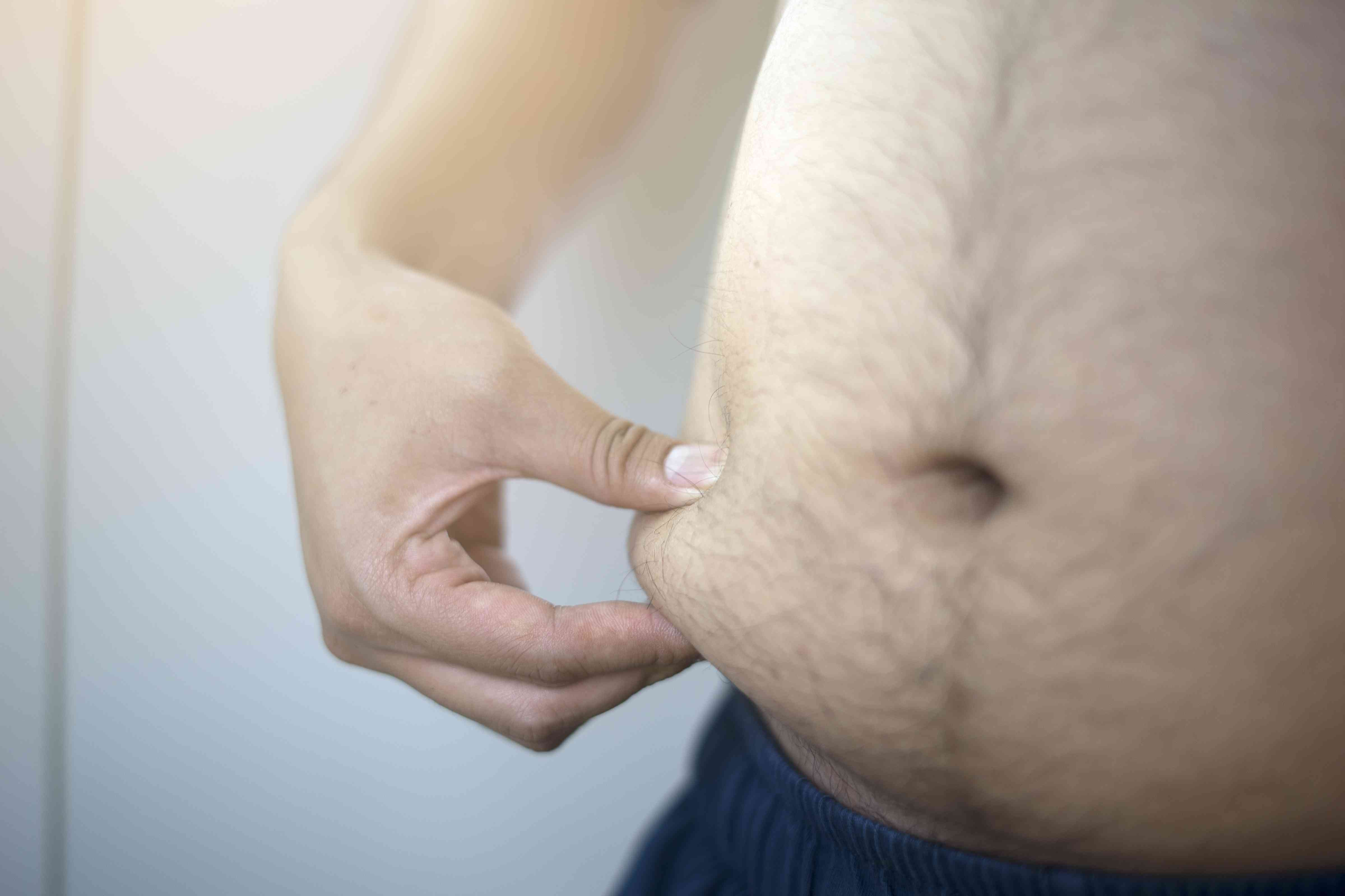 Selective focus hand touching overweight Belly
