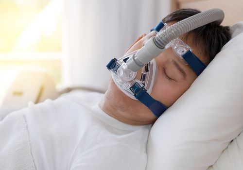 Man sleeping with BiPAP mask on his face
