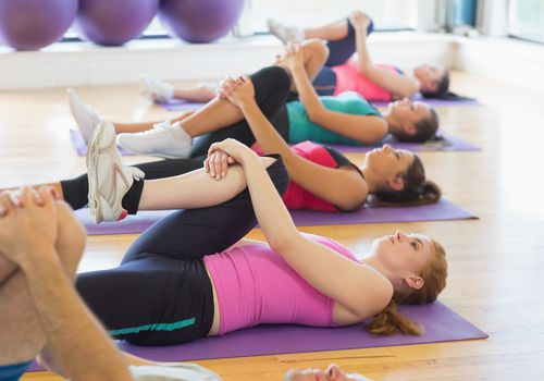 Women in supine position stretch one knee towards the chest.