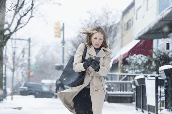 Woman walking on snowy street