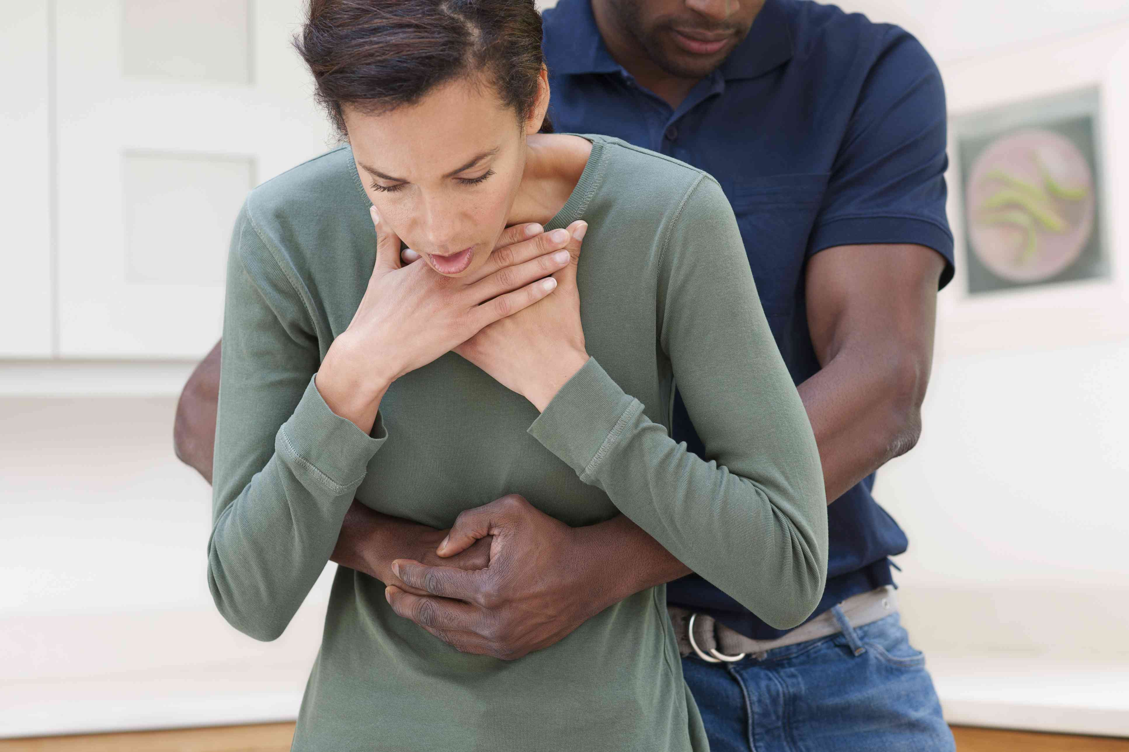 A man doing the heimlich maneuver on a woman