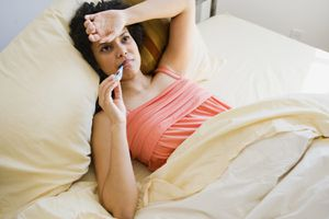 A woman sick in bed waiting to get better