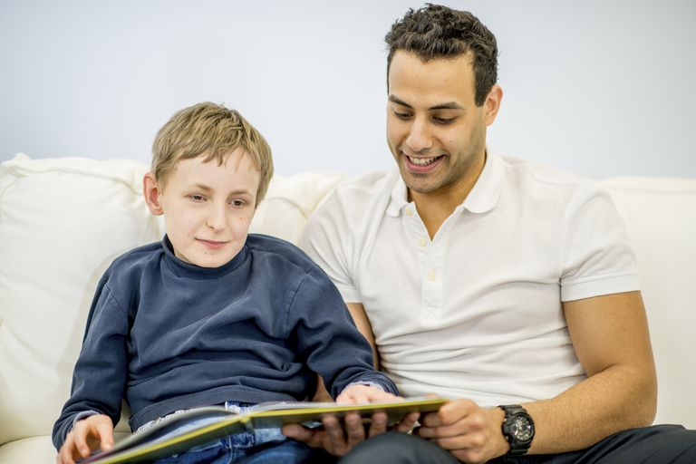 A man reading to a special needs child.