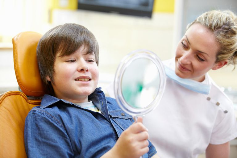 Dentist and boy patient looking in mirror