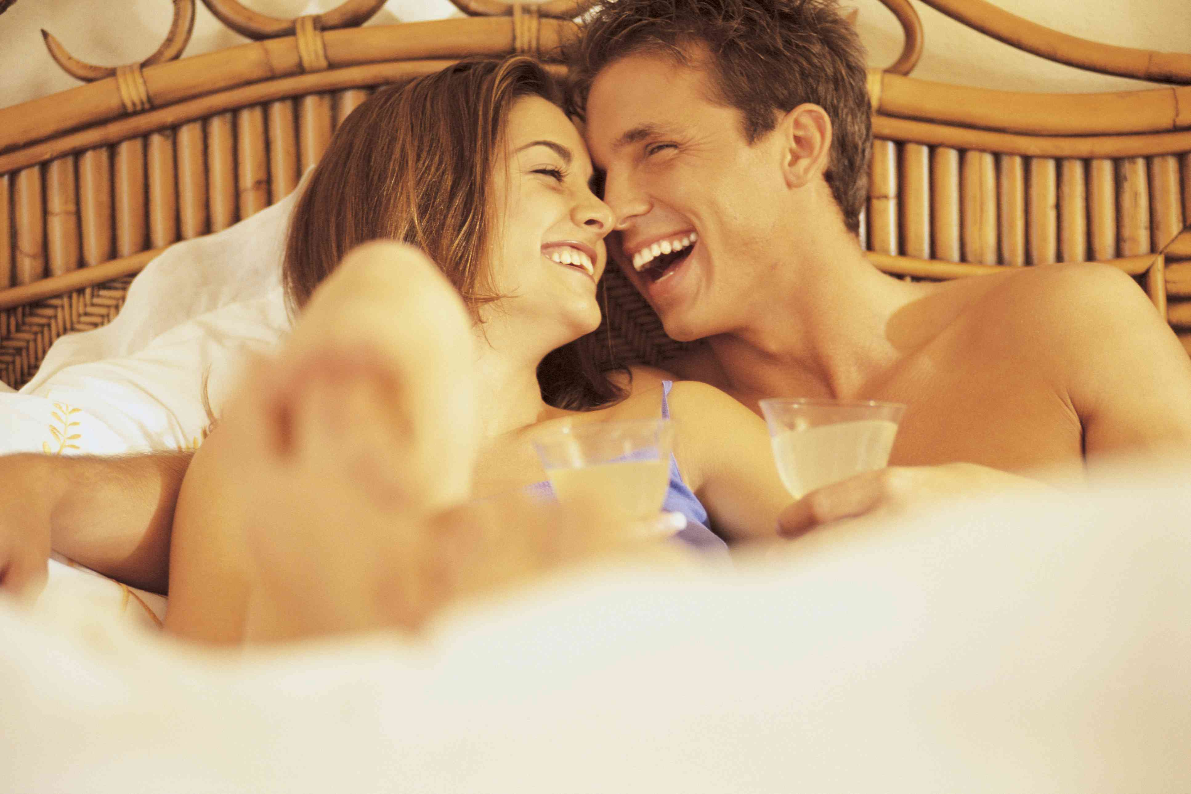 Couple in their bed with drinks