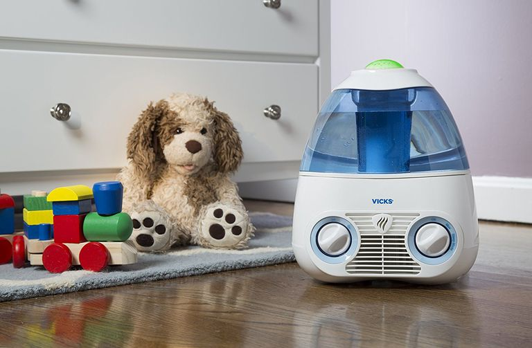 Vick's humidifier on the floor next to stuffed dog and toy train