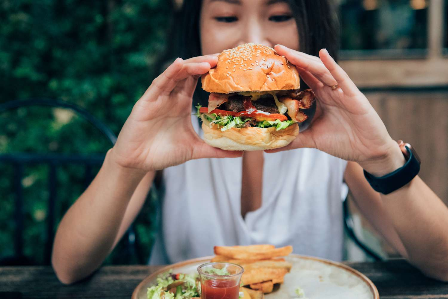 Young Woman Eating Burger At Restaurant With Outdoor Seating