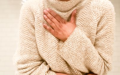 Woman short of breath with hand on her chest