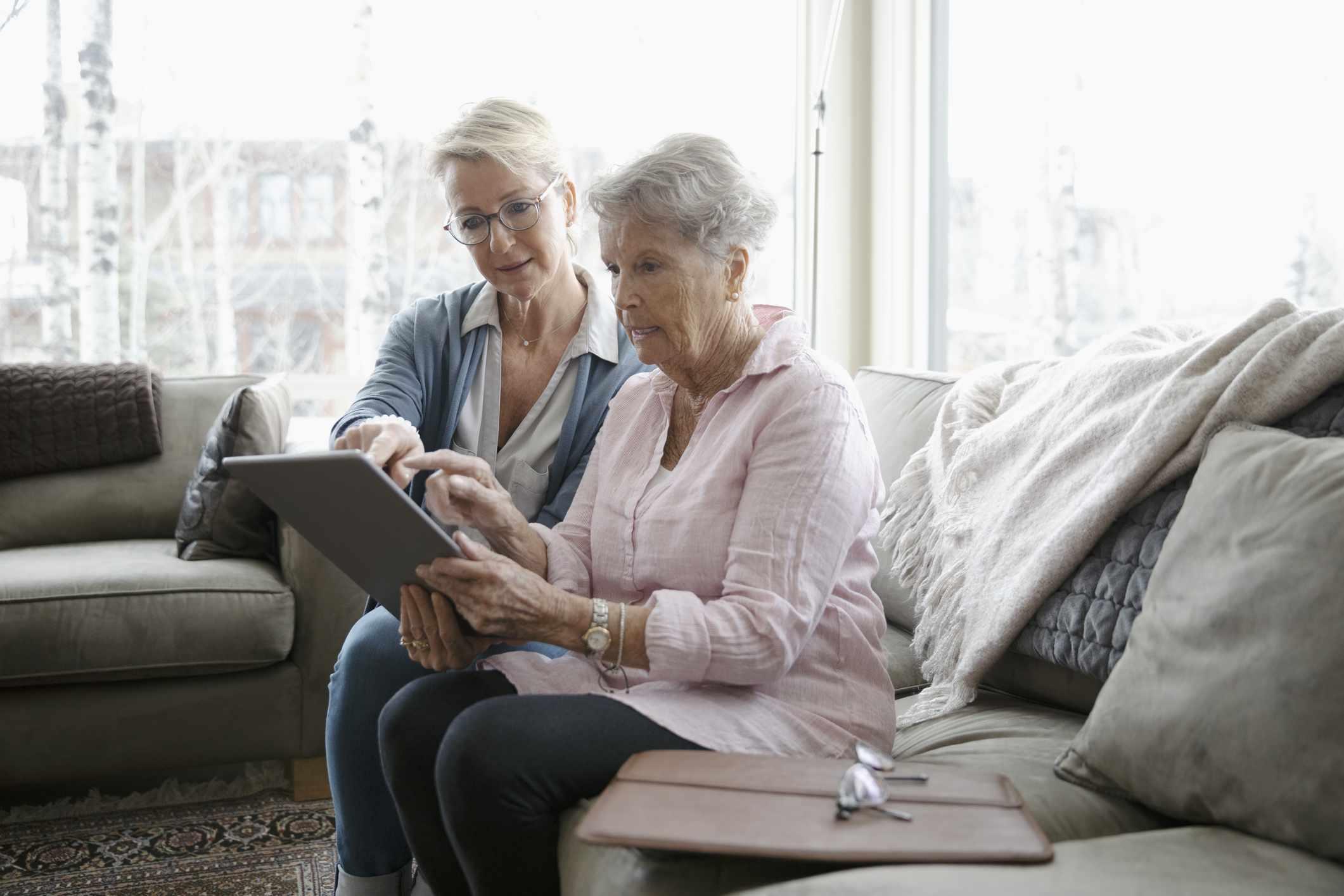 Daughter helping older mother using digital tablet in living room