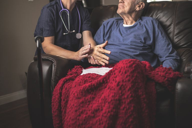 Nurse talking with older man in sitting in a chair