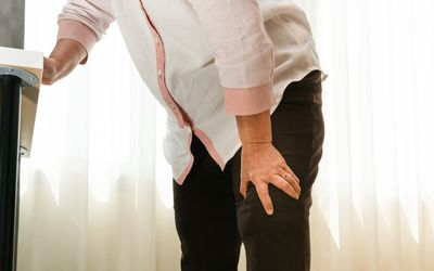 Woman bracing herself on counter due to knee pain