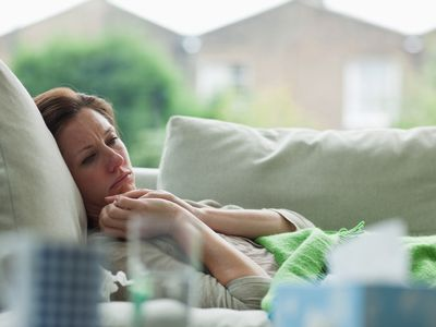 Sick-looking woman lays on the couch.