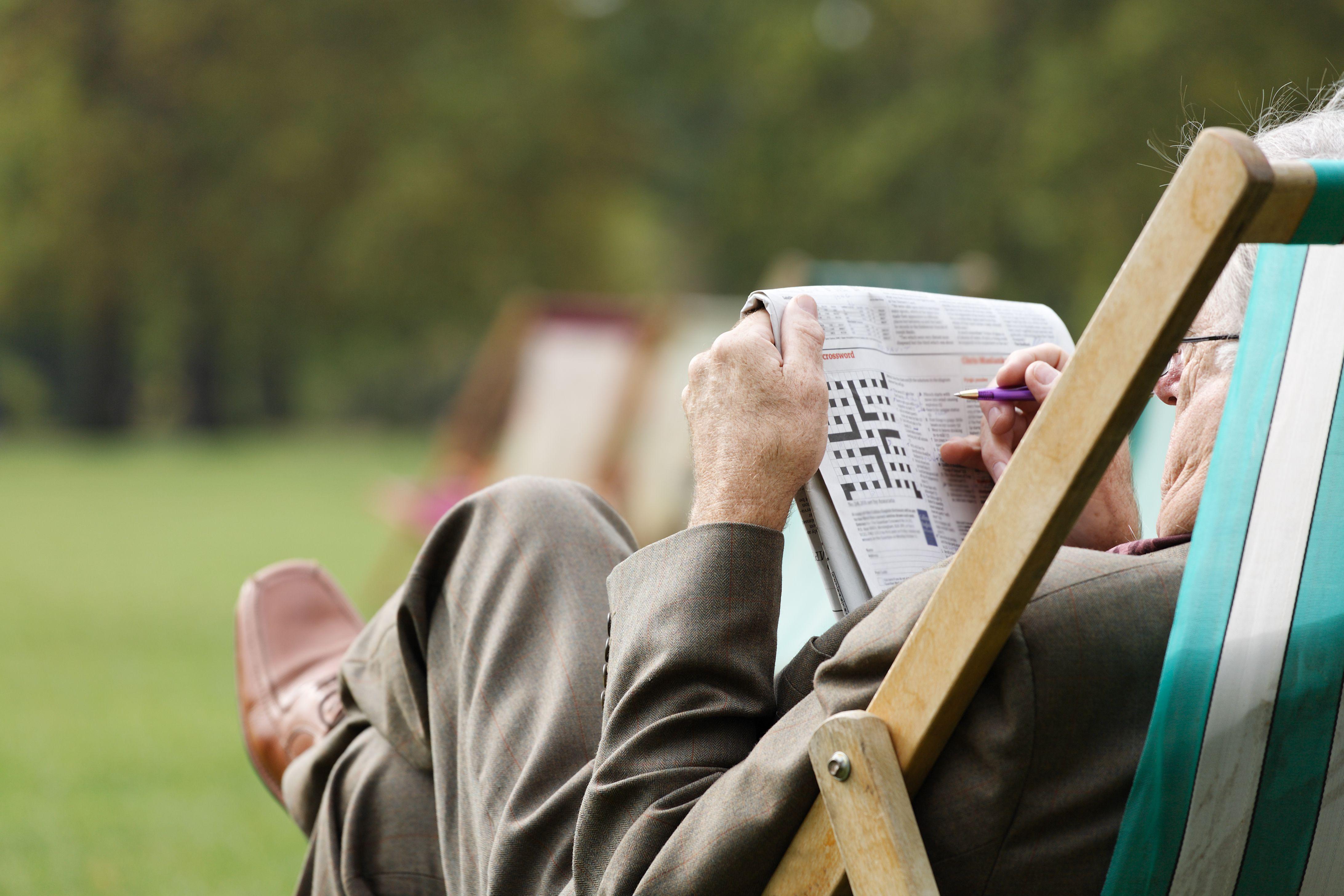 Elderly man sitting in deckchair outside doing crossword
