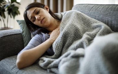 A woman lying on a couch with a blanket