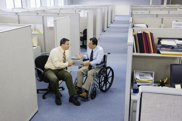 Man on wheelchair talking with co-worker