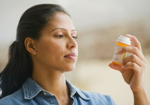 woman looking at prescription pill bottle