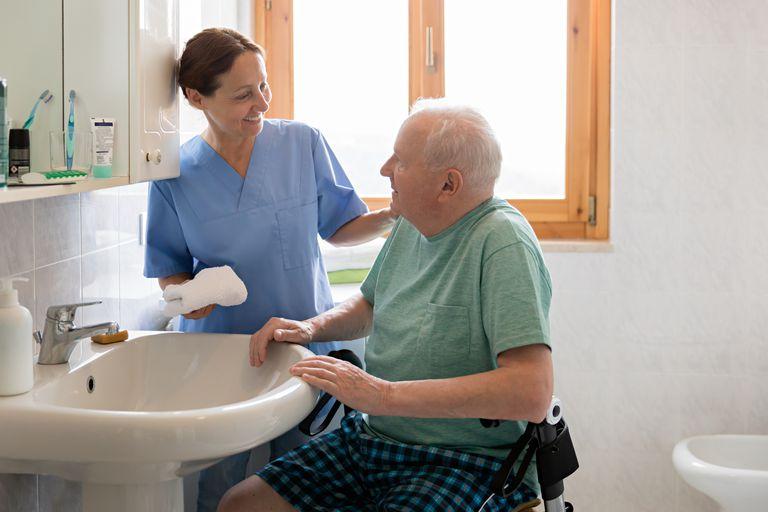 Nurse helping man wash up at a sink
