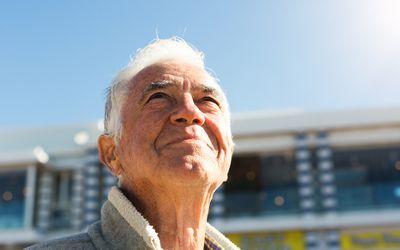 Older man squinting in bright sunlight
