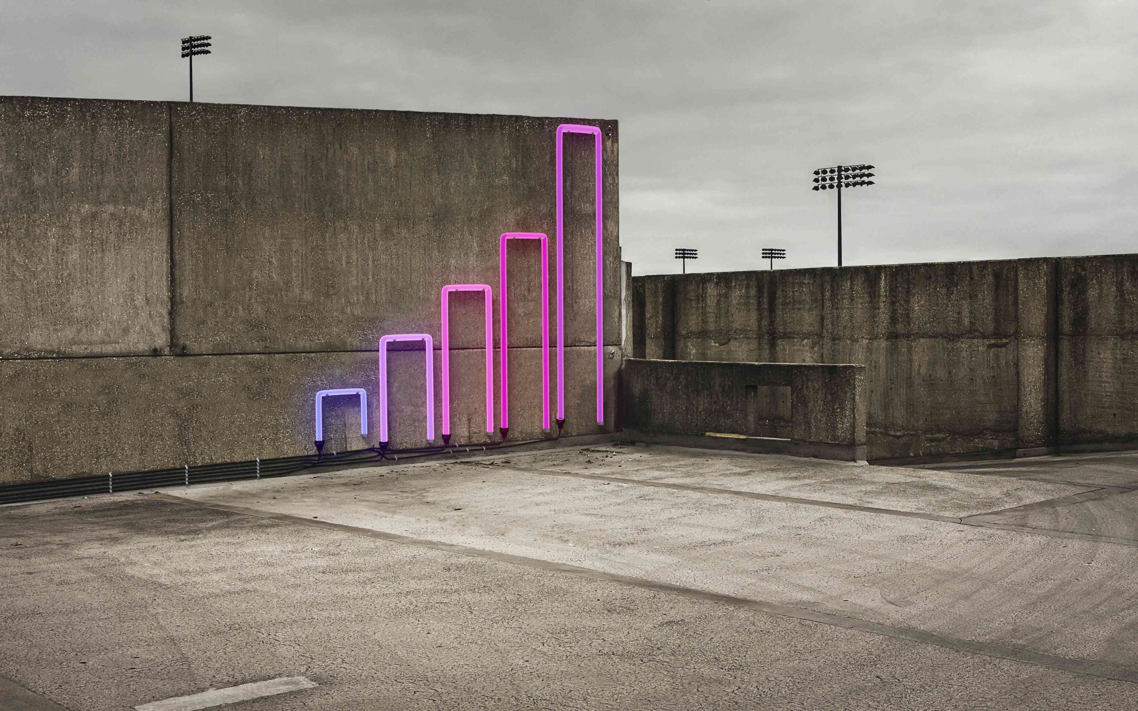 Neon sign of a bar graph on concrete wall