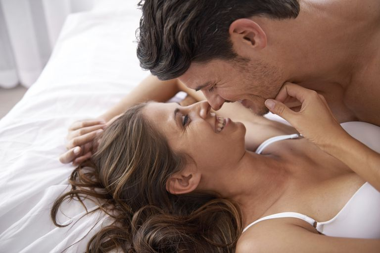 man and woman lying together on a bed