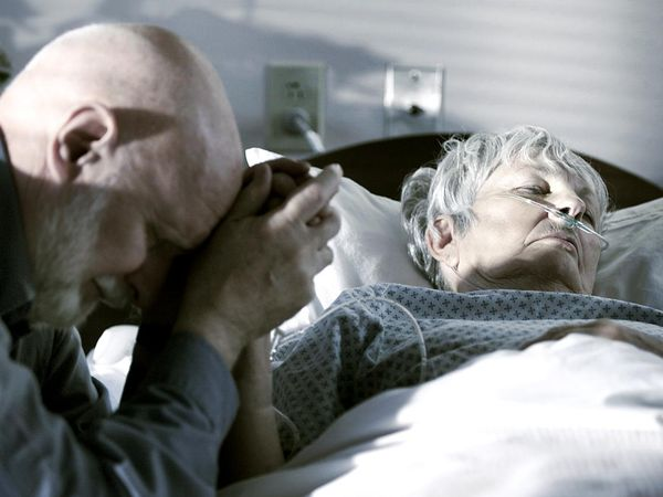 Elderly man with his wife as his wife begins the dying process