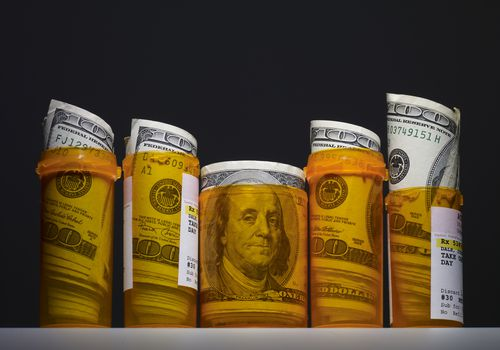 100 dollar bills rolled up in pill bottles with a black background
