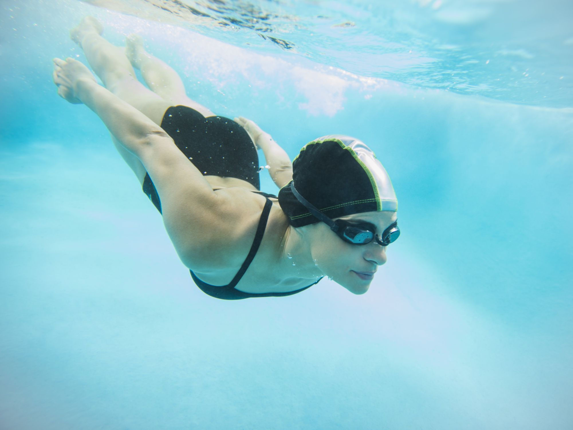 Underwater view of woman diving and swimming in a pool