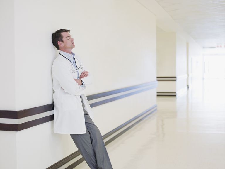 Tired doctor leaning in hospital corridor
