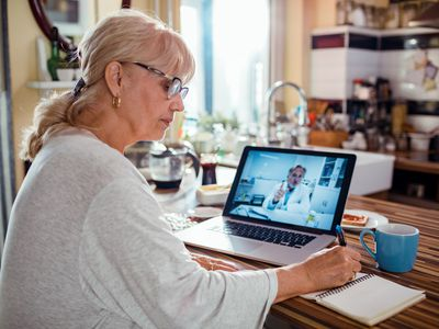 Senior woman consulting with her doctor online - stock photo