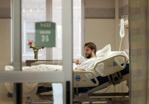 man drinking from cup in hospital