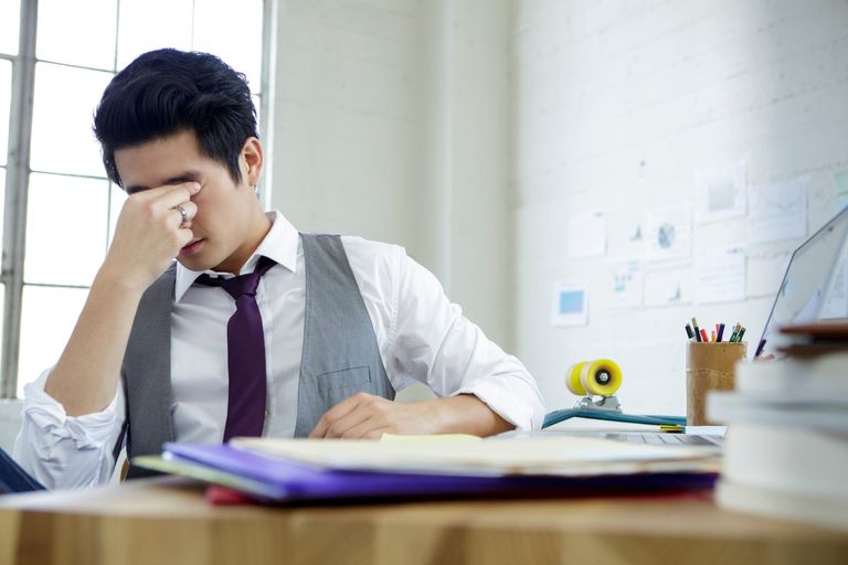 Man with migraine sitting at a desk.