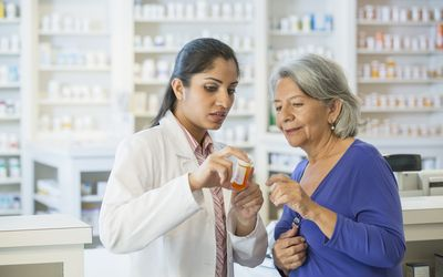 A pharmacist helps a mature customer learn how to take her prescription medication.