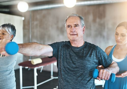 A older man using dumbbells in an exercise class