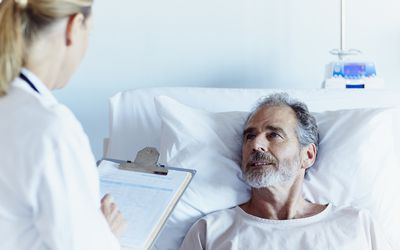 Doctor writing notes while talking to male patient : Stock Photo CompEmbedShareAdd to Board Caption:Female doctor writing notes while talking to male patient in hospital ward Doctor writing notes while talking to male patient