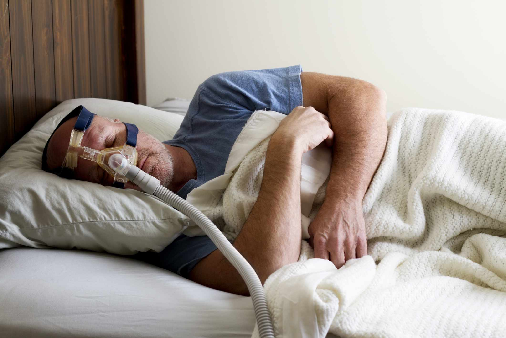 Man with sleep apnea and CPAP in bed