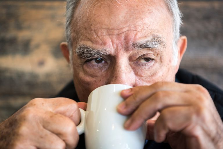 Old man having coffee or tea