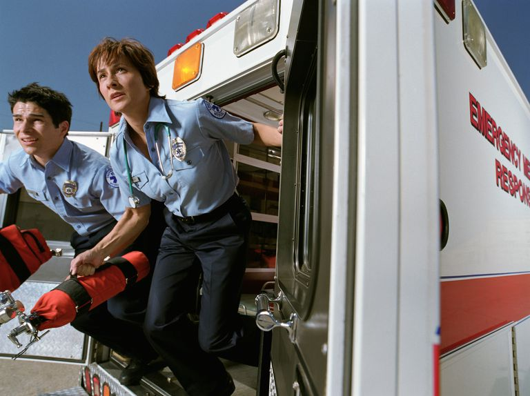 Emergency medical technicians jumping out of ambulance