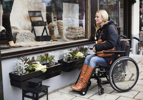 Disabled woman in wheelchair looking in store window
