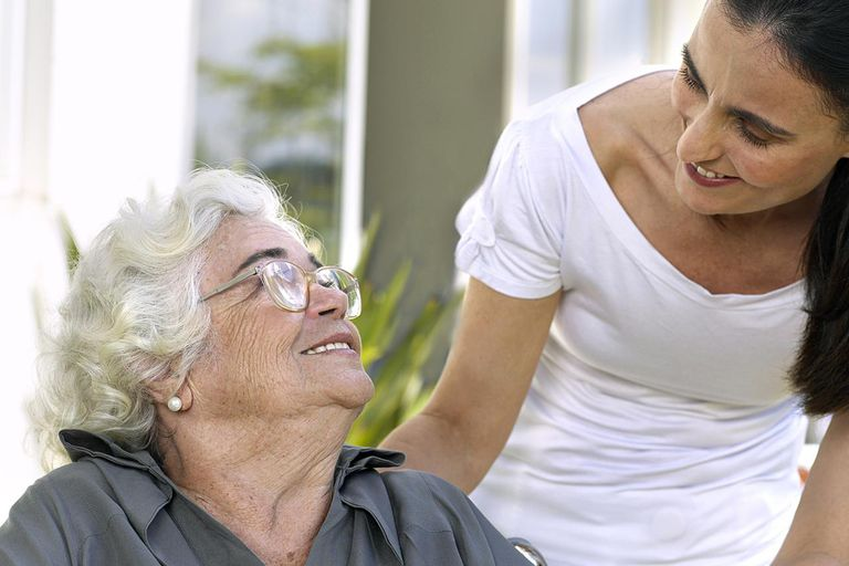Elderly woman and nurse smiling