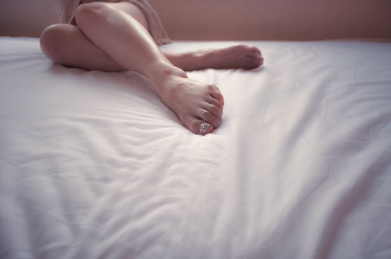 woman's legs and feet on bed