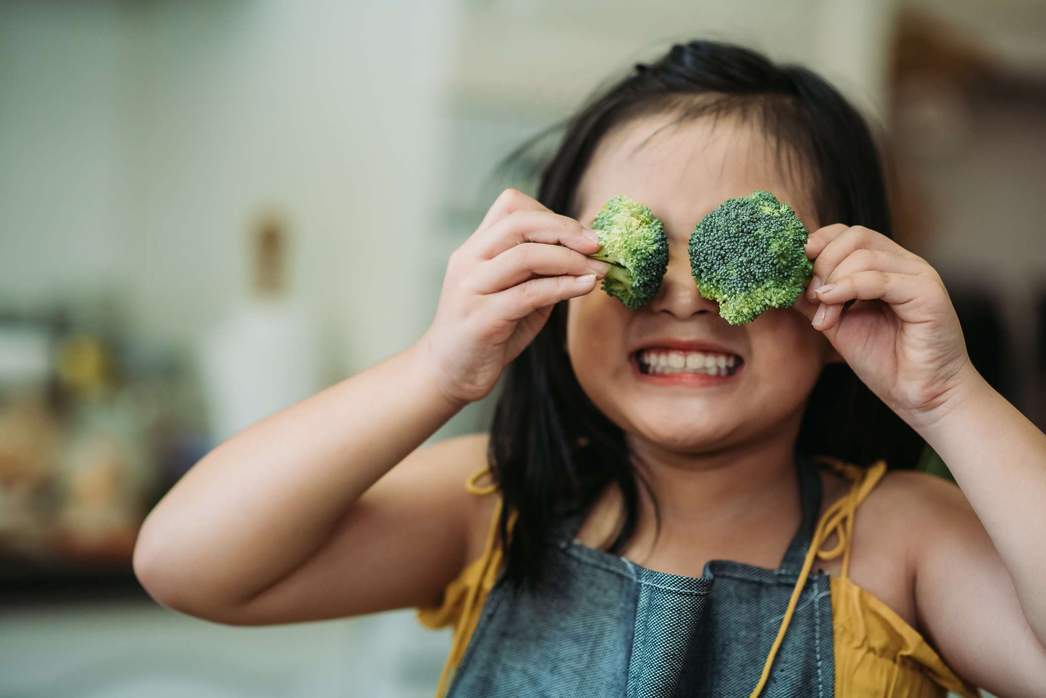 Asian chinese female child act cute with hand holding broccoli putting in front of her eyes with smiling face at kitchen