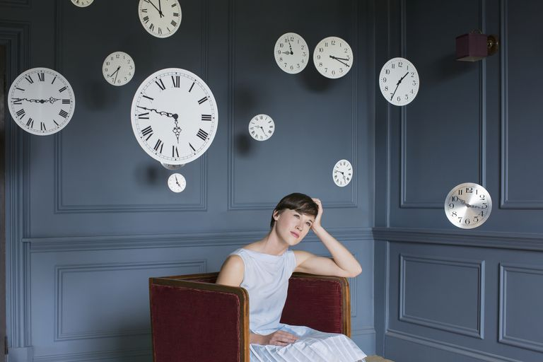 Woman surrounded by clocks.