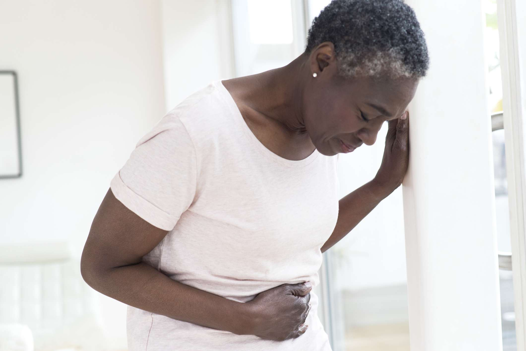 A mature woman holding her stomach in discomfort.
