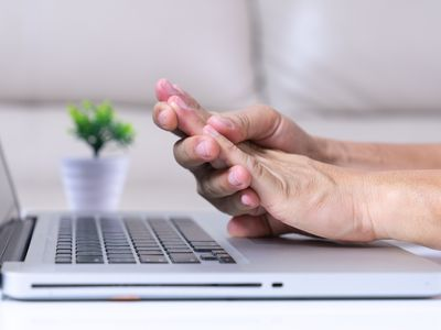 Woman clutching fingers in pain over laptop keyboard
