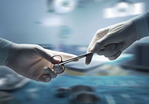 nurses hand handing a surgeon a scissors in the operating room