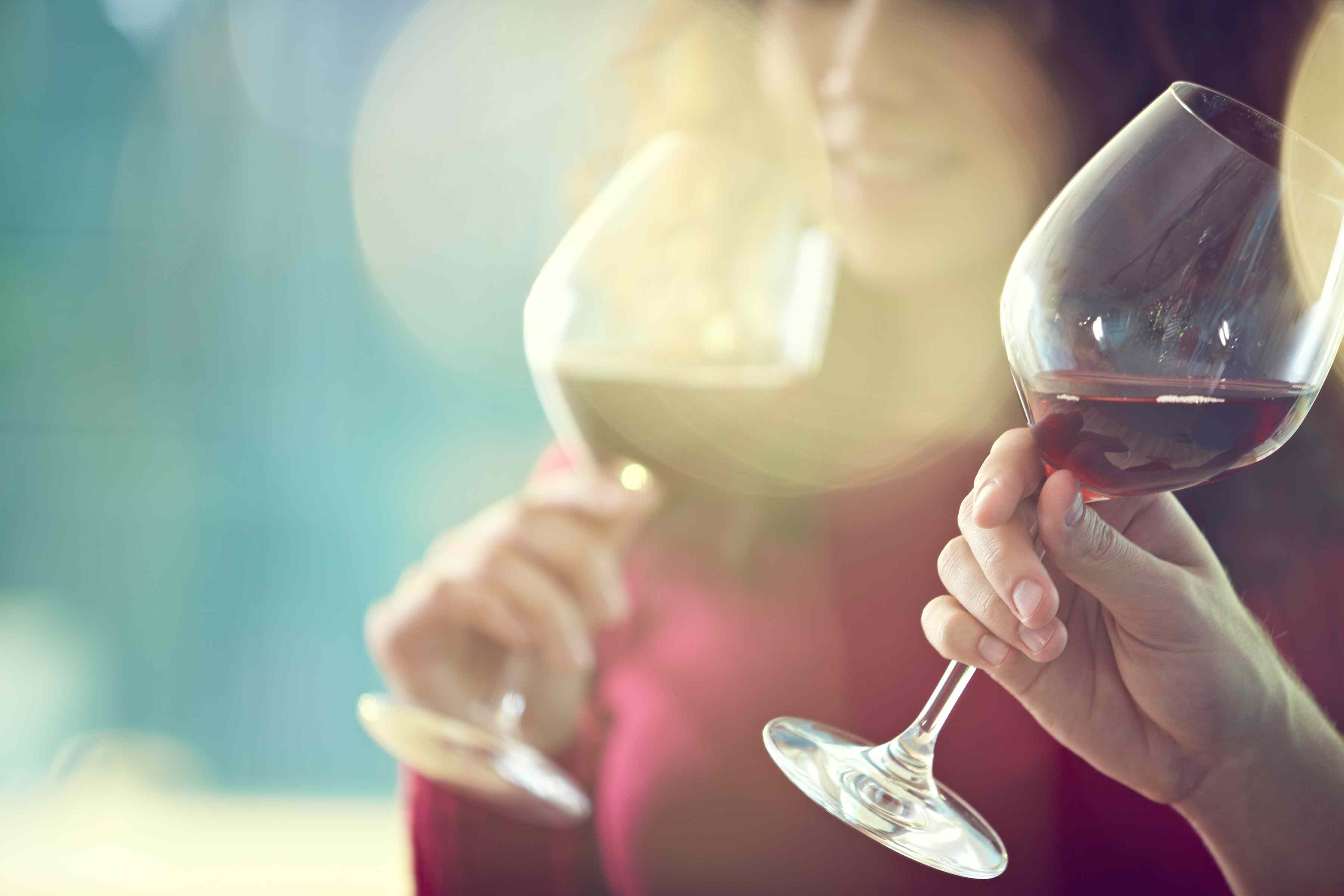 Woman drinking red wine with another person