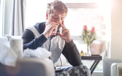 Sick man in his living room using nasal spray