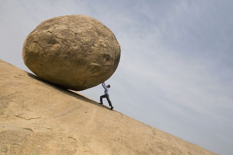 Concept of a man pushing a large boulder up hill
