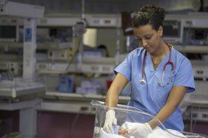 African American female nurse examining premature baby